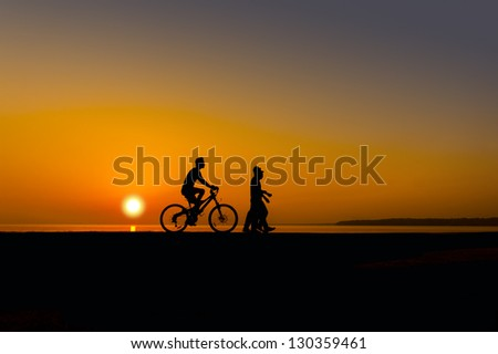 cyclist and walker silhouette on sunset - stock photo