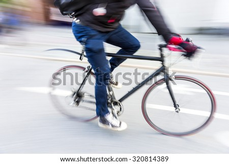 cyclist at high speed on racing bike with red tires in blurred motion