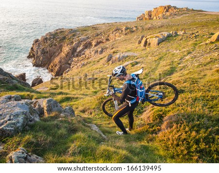 Cyclist carrying your bike on the Galician coast. The man is in a nice setting and practice mountain bike. - stock photo