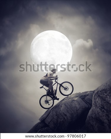 Cyclist climbing a rock under the moonlight - stock photo