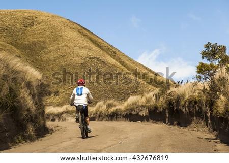 Cyclist climbing mountain road in Ecuadorian Andes - stock photo