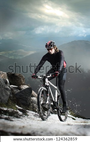 Cyclist climbing on a rock - stock photo