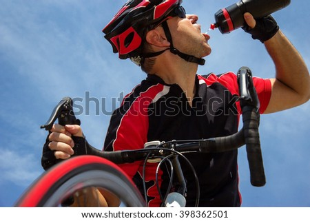 Cyclist drinking from a bottle while riding a bike. Exhausted cyclist having a drink from a bottle on a background of blue sky. Energy drink for cyclists. Biker drinking water from a bottle.. - stock photo