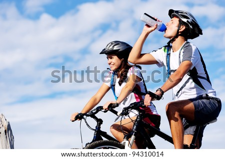 Cyclist drinking water to ensure hydration and to quench thirst. - stock photo