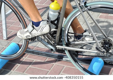 cyclist exercising on a bike with special training apparatus outdoors - stock photo