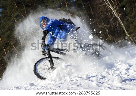 Cyclist extreme riding on mountain bike in sunny snow forest - stock photo
