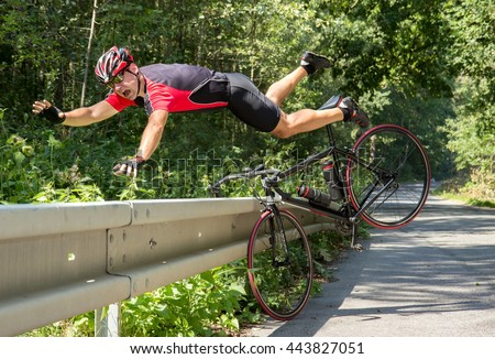 Cyclist falls off the bike into bushes. Accident on the road. Biker fall from the bike into the grass. Bicycle accident when falling through road barriers. - stock photo
