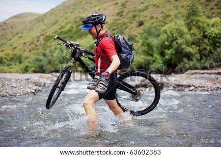 Cyclist goes over the mountain river ford - stock photo