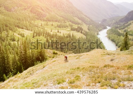 Cyclist going down the slope on a background of beautiful mountains and rivers - stock photo