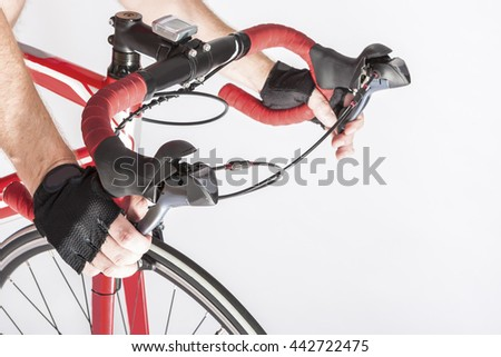 Cyclist Hands in Protective Gloves Put on Handlebars. Pressing Front and Rear Brakes Levers. Against White. Horizontal Image Orientation