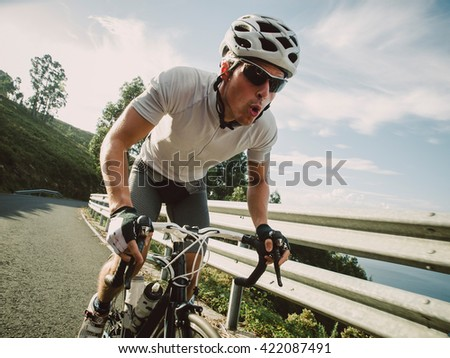 Cyclist in maximum effort pedaling outdoors in a sunny day - stock photo