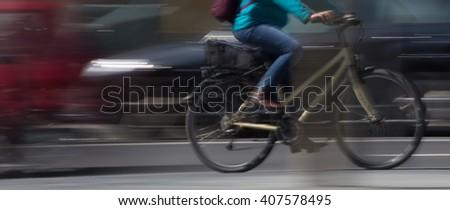 cyclist in metropolitan traffic motion blur  - stock photo