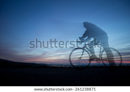 cyclist in motion blur in blue sky  - stock photo