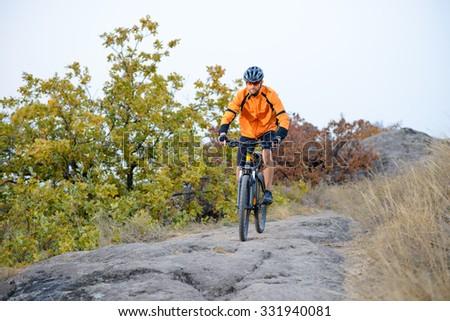 Cyclist in Orange Wear Riding Bike on the Beautiful Autumn Mountain Trail - stock photo
