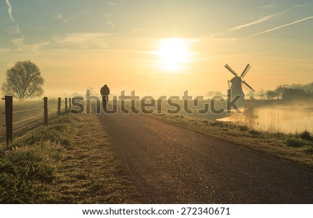 Cyclist in the Dutch countryside near a windmill just after a foggy, spring sunrise.