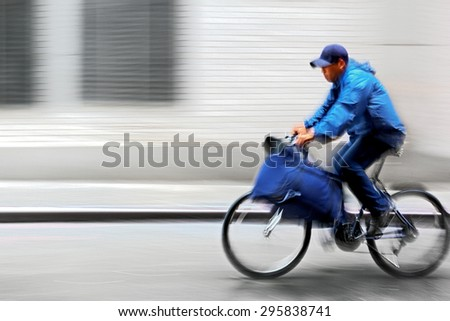 cyclist in traffic on the city roadway and delivery service motion blur - stock photo