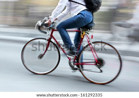 cyclist in traffic on the city roadway  motion blur  - stock photo