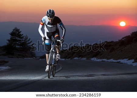 Cyclist man riding mountain bike at sunset on a mountain road - stock photo