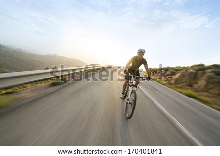 Cyclist man riding mountain bike in sunny day on a mountain road. Image with flare. - stock photo