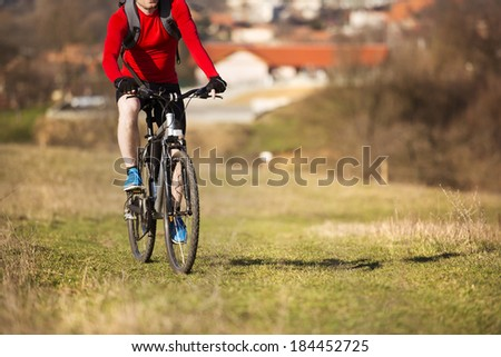 cyclist man riding mountain bike on outdoor trail in nature - stock photo