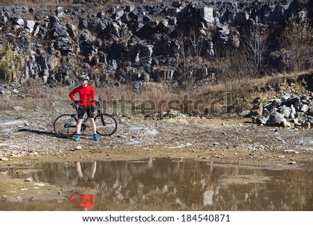 cyclist man standing with his bike and reflecting in water puddle - stock photo