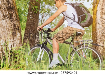 Cyclist man with backpack riding mountain bike in summer forest, theme of sport and hiking