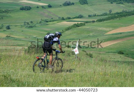 Cyclist on a bike on a hill in summer sunny day - stock photo