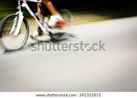 Cyclist on a road bike going fast (motion blur technique is used to convey movement; colour toned image) - stock photo