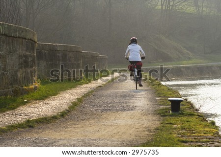 Cyclist on a towpath over an aqueduct by the Forth and Clyde Canal - stock photo
