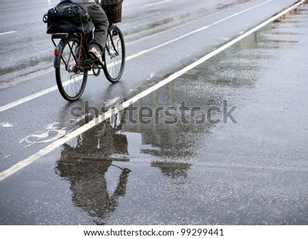 Cyclist on bicycle path on rainy day. Focus on reflection in water. - stock photo