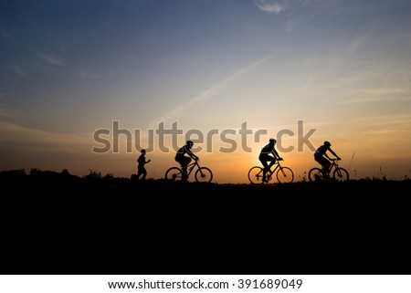 Cyclist on sunrise ,people ride bicycle on sunset background.