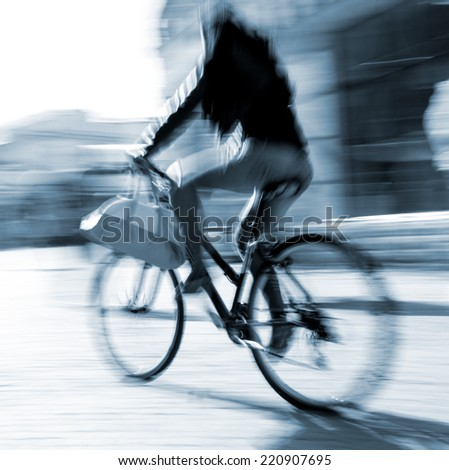 Cyclist on the city roadway in motion blur - stock photo