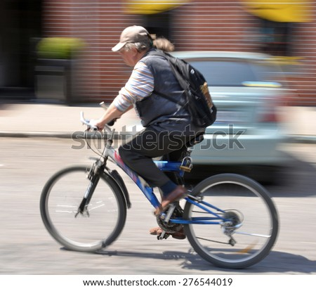 Cyclist on the city roadway. Intentional motion blur - stock photo