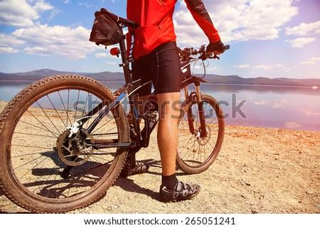 cyclist on the shore of a mountain lake. man outdoors. mountain bike - stock photo