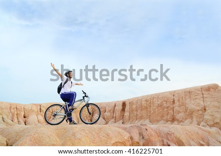 Cyclist on the top of a hill with his hands up - stock photo