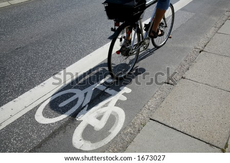 Cyclist passing by on urban cycle path. - stock photo