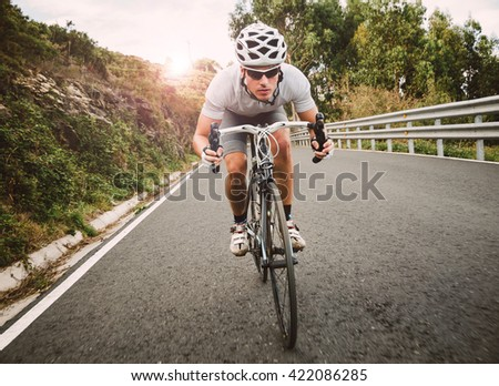 Cyclist pedaling on a racing bike outdoors in a sunny day - stock photo