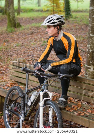 Cyclist resting on a bench in nature. Man is looking aside. - stock photo