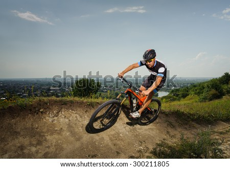 Cyclist rides downhill in the mountains - stock photo