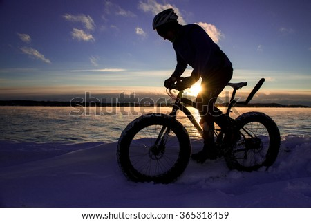 Cyclist rides fat tire bike in winter at sunset - stock photo