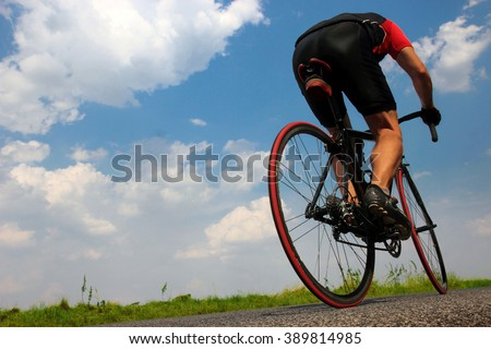Cyclist rides on asphalt road. Road cyclist on a background of blue sky. Racer bicycle. The rear part of a fast-moving cyclists. Back of biker on bike. Bicyclist riding a bike in the summer  - stock photo
