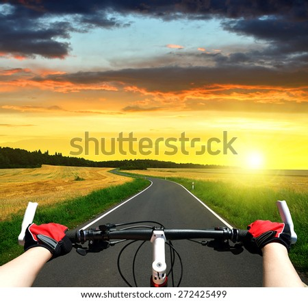 Cyclist riding a bike in the sunset - stock photo