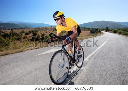 Cyclist riding a bike on an open road - stock photo