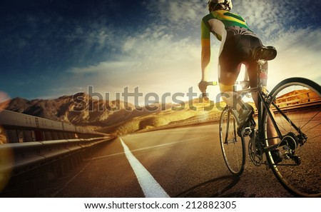 Cyclist riding a bike on an open road to the sunset  - stock photo
