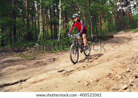 cyclist riding a mountain bike along the forest road. the effect of motion blur - stock photo