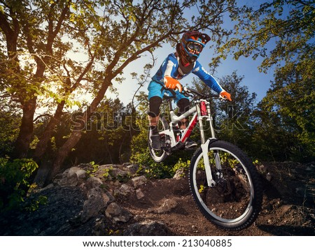 Cyclist riding a mountain bike downhill style. Extreme sports on a bicycle outdoors.