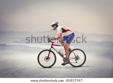Cyclist riding a mountain bike in a desert - stock photo