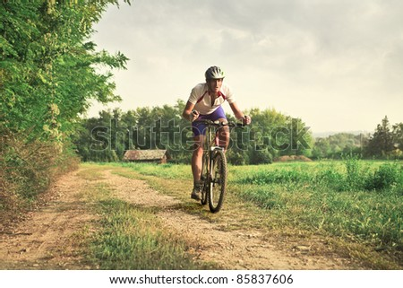 Cyclist riding a mountain bike on a countryside road - stock photo