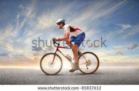 Cyclist riding a mountain bike ona street - stock photo
