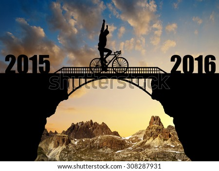Cyclist riding across the bridge at sunset. Forward to the New Year 2016 - stock photo